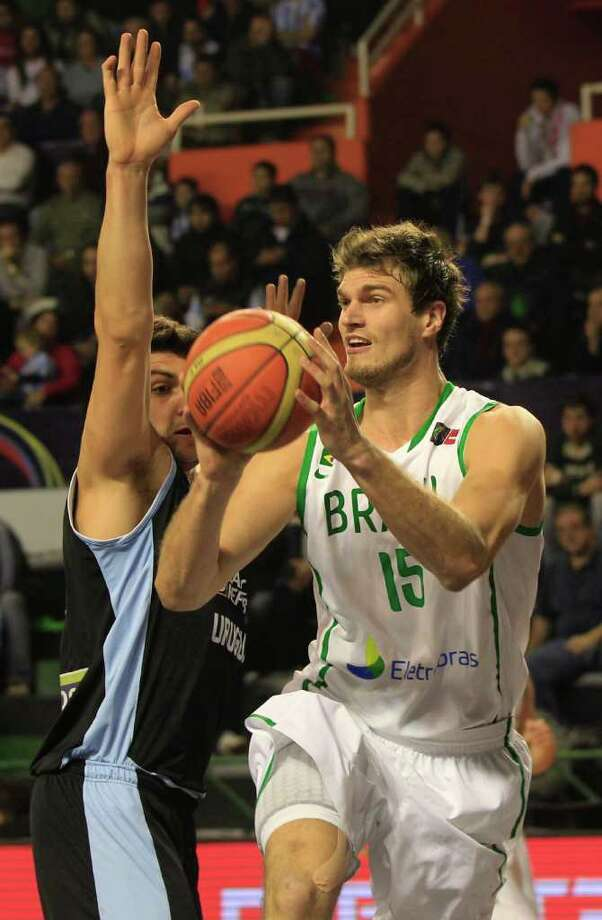 Brazil's Tiago Splitter, right, is blocked by Uruguay's Esteban Batista during a FIBA Americas Championship basketball game in Mar del Plata, Argentina, Monday, Sept. 5, 2011. The top two finishers of the tournament get an automatic berth in the 2012 London Olympics and the next three advance to the last-chance Olympic qualifier to be held in July 2012. Photo: Martin Mejia/Associated Press