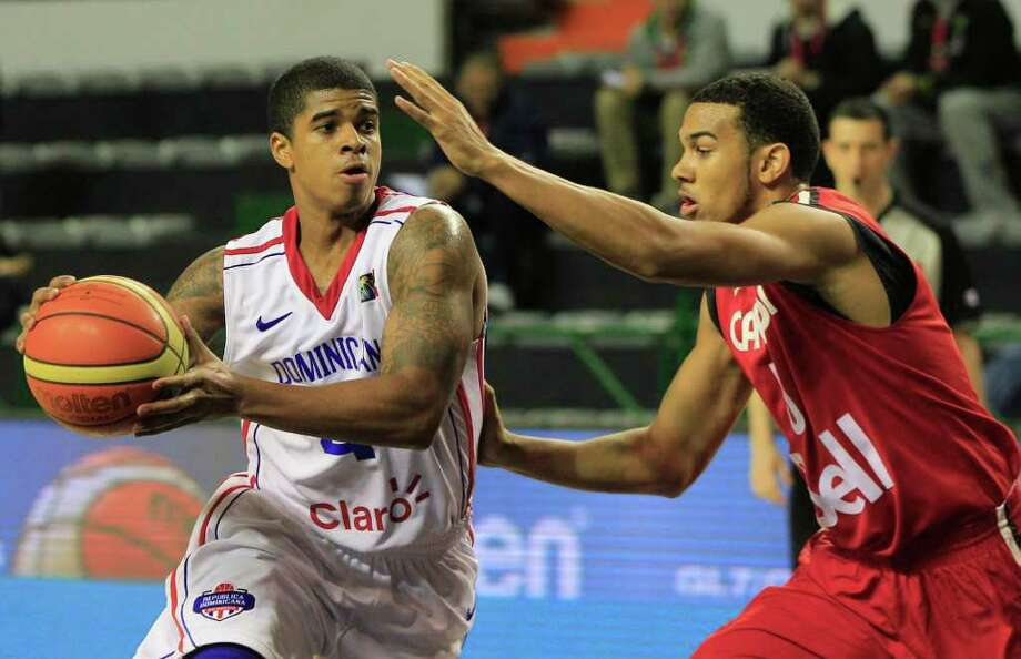 Dominican Republic's Edgar Sosa, left, dribbles around Canada's Cory Joseph during a FIBA Americas Championship basketball game in Mar del Plata, Argentina, Thursday, Sept. 1, 2011. The top two finishers of the tournament get an automatic berth in the 2012 London Olympics and the next three advance to the last-chance Olympic qualifier to be held in July 2012. Photo: Martin Mejia/Associated Press