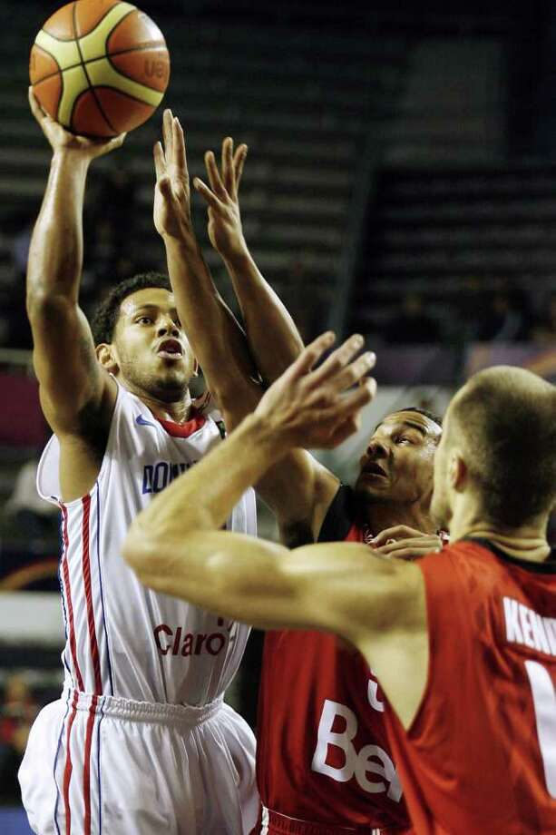 The Dominican Republic's Ronald Ramon (left) shoots at the basket as Canada's Cory Joseph and another Canadian player block during a qualifying round match of the 2011 FIBA Americas Championship on Thursday, Sept. 1, 2011 at Islas Malvinas Stadium, Mar del Plata, Buenos Aires, Argentina. Photo: Maxi Failla/AFP/Getty Images / 2011 AFP