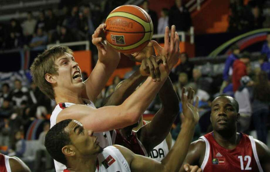 Canada's Kelly Olynyk, top, struggles for a rebound with Cuba's Luis Yoan, behind partially covered, as Canada's Cory Joseph, front, looks on during a FIBA Americas Championship basketball game in Mar del Plata, Argentina, Friday Sept. 2, 2011. The top two finishers of the tournament get an automatic berth in the 2012 London Olympics and the next three advance to the last-chance Olympic qualifier to be held in July 2012. Photo: Martin Mejia/Associated Press
