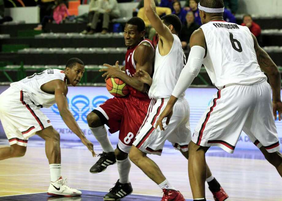 Cuba's Yorman Polas, second from left, tries to move the ball past Canada's Jevohn Shepherd, left, Cory Joseph, second from right, and Jeffrey Ferguson, right, during a FIBA Americas Championship basketball game in Mar del Plata, Argentina, Friday Sept. 2, 2011.  The top two finishers of the tournament get an automatic berth in the 2012 London Olympics and the next three advance to the last-chance Olympic qualifier to be held in July 2012. Photo: Martin Mejia/Associated Press