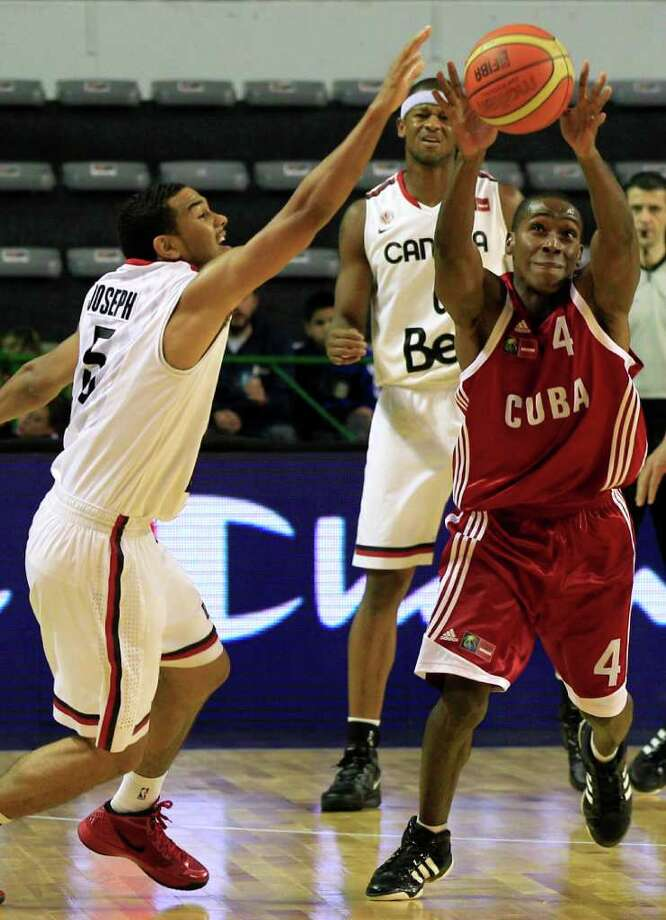 Cuba's Alexis Mestre, right, struggles for control of the ball with Canada's Cory Joseph during a FIBA Americas Championship basketball game in Mar del Plata, Argentina, Friday Sept. 2, 2011.  The top two finishers of the tournament get an automatic berth in the 2012 London Olympics and the next three advance to the last-chance Olympic qualifier to be held in July 2012. Photo: Martin Mejia/Associated Press