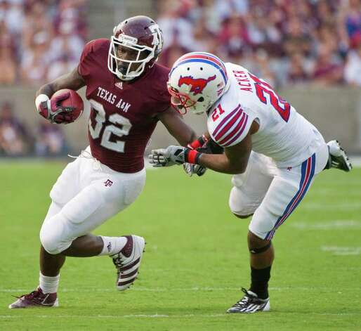 Texas A&M's Cyrus Gray (left) fends off SMU's Kenneth Acker during Sunday's 132-yard outing. Photo: Dave Einsel/Associated Press