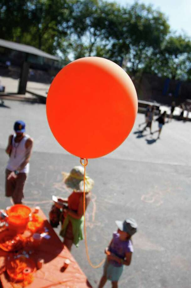 A young girl receives an orange balloon from the Sutton Beres Culler table at Bumbershoot 201. Volunteers passed out free balloons as part of a visual art project at Bumbershoot. Photo: JOE DYER / SEATTLEPI.COM