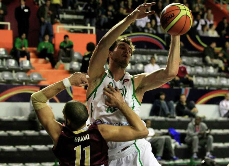 Brazil's Tiago Splitter, right, battles for a rebound with Venezuela's Jose Bravo at a FIBA Americas Championship basketball game in Mar de Plata, Argentina, Tuesday Aug. 30, 2011. Photo: Martin Mejia/Associated Press
