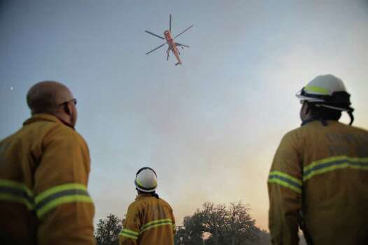 Firefighters from the Coppell Fire Department watch as an S-64 Skycrane helicopter drops a fire retardant to help contain a wildfire burning through parts of Cedar Creek, Texas Monday afternoon Sept. 5, 2011.  At least 5,000 people were forced from their homes in Bastrop County about 25 miles east of Austin, and about 400 were in emergency shelters, officials said.  (AP Photo/Tamir Kalifa/The Daily Texan) Photo: Tamir Kalifa, Associated Press / The Daily Texan
