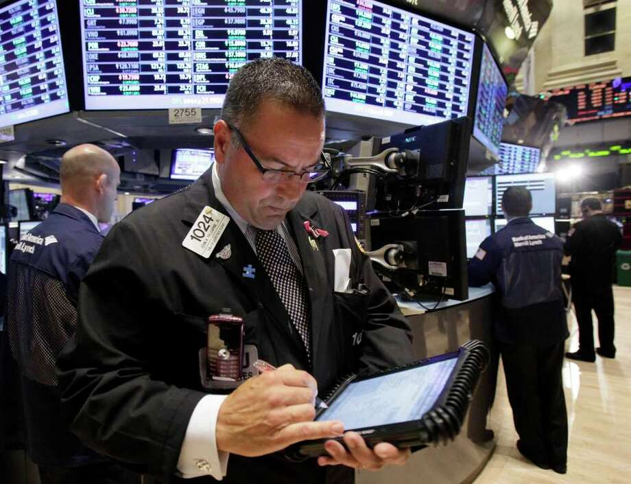 In this Aug. 29, 2011 photo, trader John Yaccarine, center, works on the floor of the New York Stock Exchange. The Swiss franc dropped sharply Tuesday, Sept. 6, 2011, after the country's central bank pegged it against the euro, while European stocks recovered their poise following a drubbing the previous session, when investors fretted over the exposure of banks to the debt of countries like Greece and Italy.(AP Photo/Richard Drew) Photo: Richard Drew, STF / AP