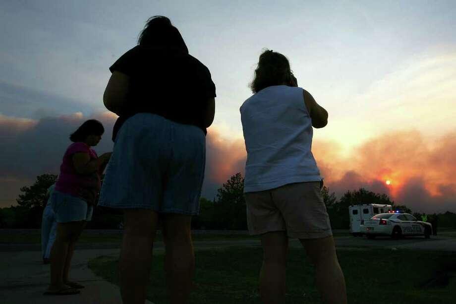 Residentes del área de Magnolia, al norte de Houston, observan el incendio forestal  desde la intersección de las rutas FM 1488 y FM 1774. El incendio, uno de los varios que afecta a Texas, abarca unos 300 acres y obligó a la evacuación de unos 8,000 residentes. Photo: Karl Anderson, MBR / AP