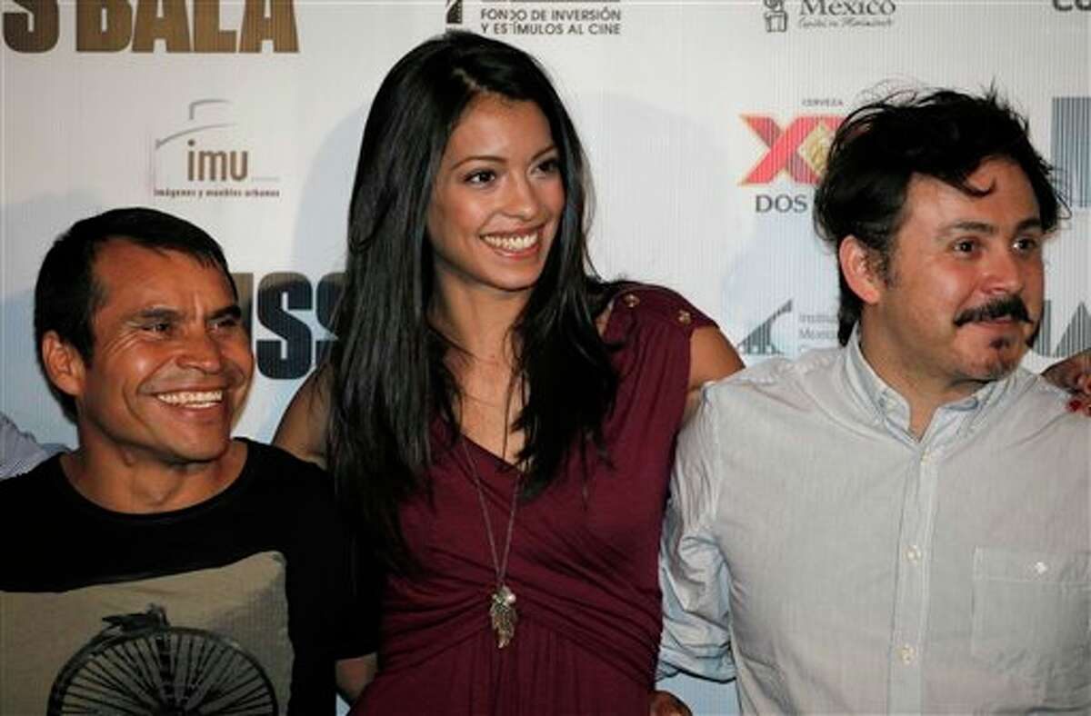 """Mexican actors, from left, Noe Hernandez, Stephanie Sigman, and director Gerardo Naranjo pose for pictures during a press conference to promote """"Miss Bala"""" film in Mexico City, Monday, Sept. 5, 2011. Miss Bala will be released on Sep. 9 in Mexico. (AP Photo/Eduardo Verdugo)"""