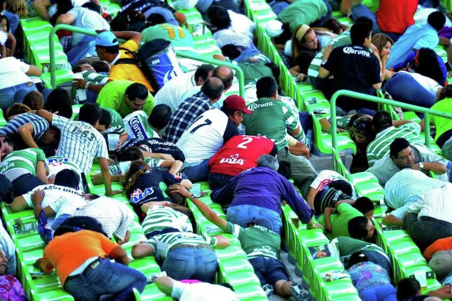 AP /El Siglo de Torreón aficionados: buscaron protección entre las butacas durante el tiroteo, en el partido entre Santos y Morelia. Photo: STR / El Siglo de Torreon