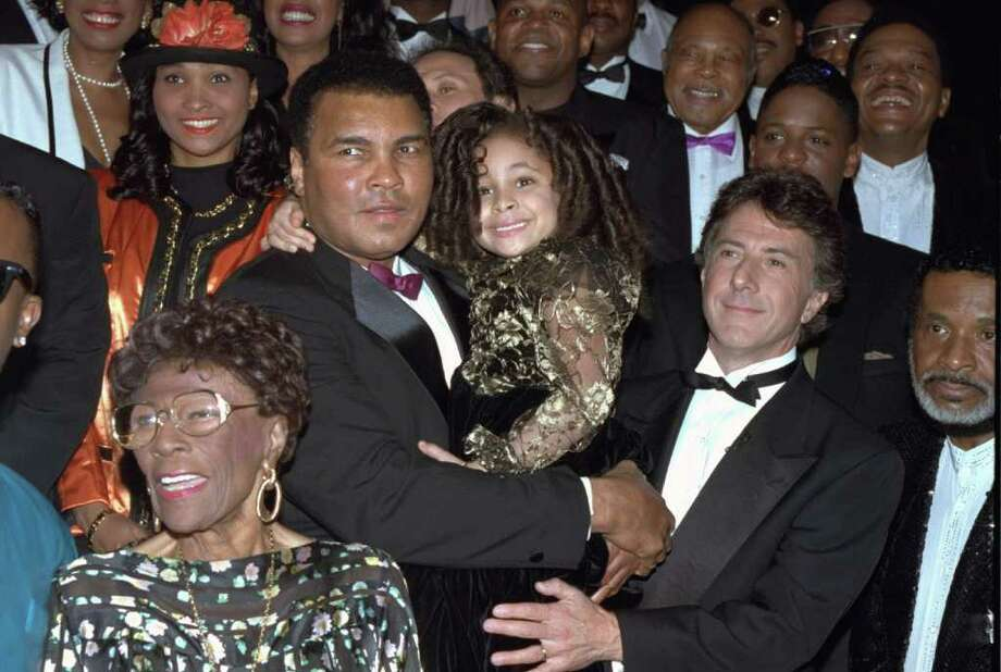 "Raven-Symone, center, shown with boxing legend Muhammad Ali, was 4 when she was cast as Olivia Kendall on ""The Cosby Show"" in 1989. She continued to appear on TV, spending five years on ""Hangin' with Mr. Cooper"" between the ages of 7 and 12, then was found on The Disney Channel in movies like ""Zenon: Girl of the 21st Century"" and ""The Cheetah Girls,"" all before the age of 18.  Photo: CHRIS MARTINEZ, STR / AP1992"