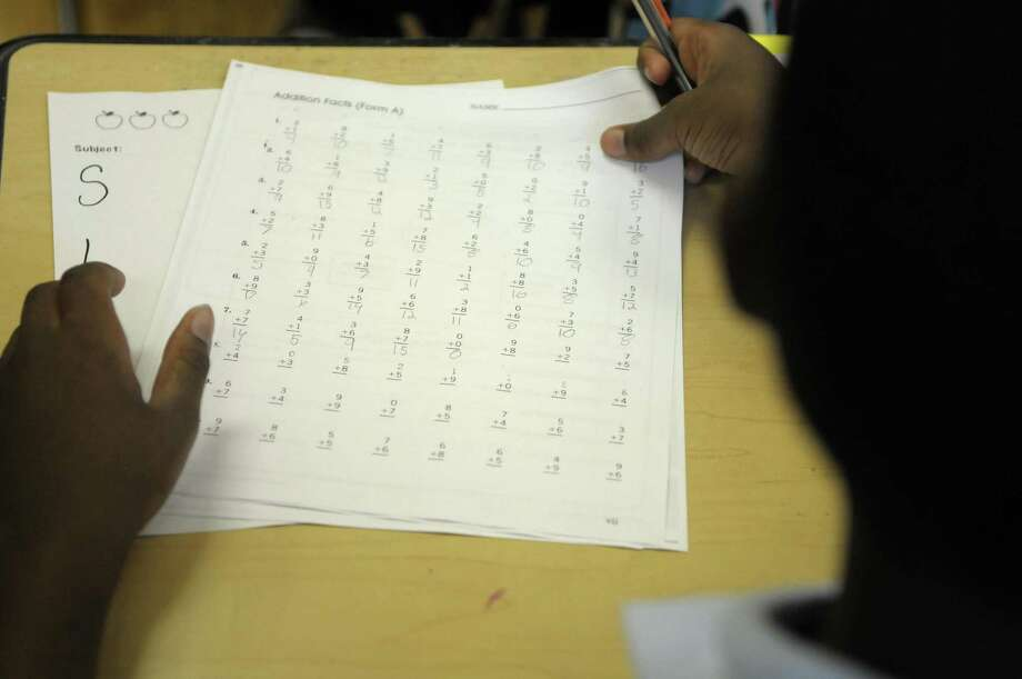A fifth-grader works on a math sheet during the first day of school Tuesday at Schuyler Achievement Academy elementary school in Albany.  (Paul Buckowski / Times Union) Photo: Paul Buckowski  / 00014514A
