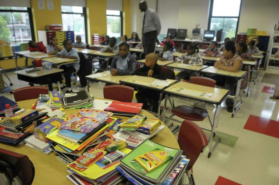 School supplies are piled high on a desk as third-graders meet the new principal, Anthony Clement, during the first day of school last fall at Schuyler Achievement Academy in Albany. (Paul Buckowski / Times Union archive)