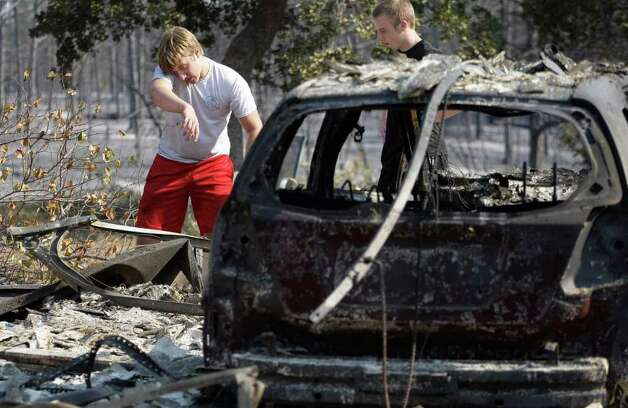 Hayden Wilhelm, left, sprays water on hot spots at a neighbors home that burned when wildfires swept through the area, Tuesday, Sept. 6, 2011, in Bastrop, Texas. More than 1,000 homes have burned in at least 57 wildfires across rain-starved Texas, officials said Tuesday. Photo: AP