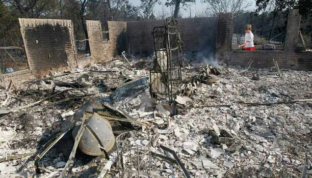 Hayden Wilhelm sprays water on hot spots at a neighbors home that burned when wildfires swept through the area, Tuesday, Sept. 6, 2011, in Bastrop, Texas.  More than 1,000 homes have burned in at least 57 wildfires across rain-starved Texas, officials said Tuesday. Photo: AP