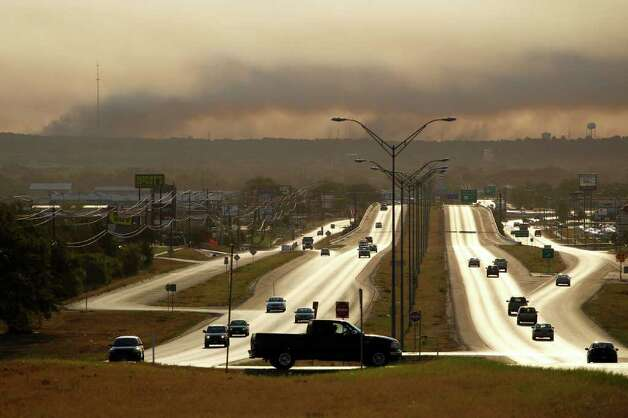 Smoke from a wildfire hangs in the sky, Tuesday, Sept. 6, 2011, in Bastrop, Texas. Officials hope that calmer winds Tuesday will help firefighters battling a wildfire that has destroyed nearly 500 homes in Central Texas and forced thousands of residents to evacuate to shelters to avoid the blaze. Photo: AP