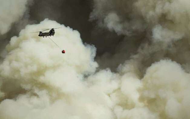 A firefighting helicopter is dwarfed by massive plumes of smoke in Bastrop, Texas, on Monday Sept. 5, 2011. A roaring wildfire raced unchecked Monday through rain-starved farm and ranchland in Texas, destroying nearly 500 homes during a rapid advance fanned in part by howling winds from the remnants of Tropical Storm Lee. (AP Photo/Austin American-Statesman, Jay Janner)  MAGS OUT; NO SALES; TV OUT; INTERNET OUT EXCEPT AP MEMBERS Photo: AP