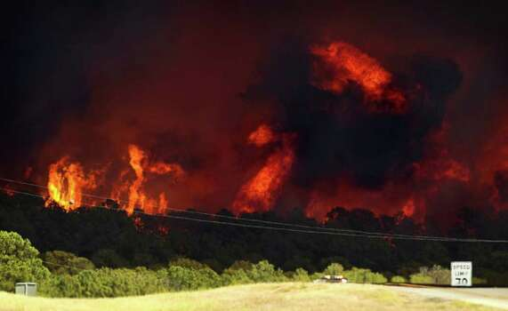 A fire rages near Highway 71 east of Bastrop, Texas, on Monday Sept. 5, 2011. A roaring wildfire raced unchecked Monday through rain-starved farm and ranchland in Texas, destroying nearly 500 homes during a rapid advance fanned in part by howling winds from the remnants of Tropical Storm Lee. (AP Photo/Austin American-Statesman, Jay Janner)  MAGS OUT; NO SALES; TV OUT; INTERNET OUT EXCEPT AP MEMBERS Photo: AP