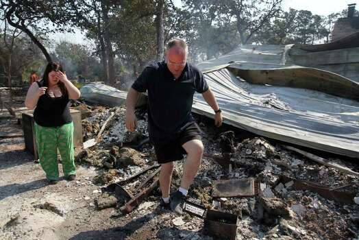 Robert Martin (right) and Katie Key (left) look over the burned down remains of the home that Key grew up in in the Bluebonnet Acres subdivision west of Bastrop, Texas Tuesday September 6, 2011. The home, at 527 Leisure Lane, is owned by Key's stepfather Larry Graf. Hundreds of homes have burned down and thousands of acres of land have destroyed by wildfires that have swept through the area. JOHN DAVENPORT/jdavenport@express-news.net Photo: JOHN DAVENPORT, SAN ANTONIO EXPRESS-NEWS / SAN ANTONIO EXPRESS-NEWS (Photo can be sold to the public)