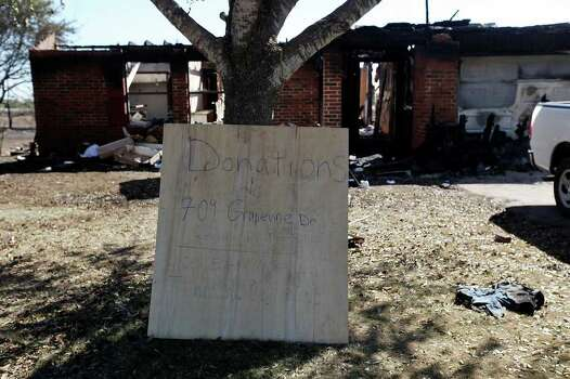 A sign is placed in front of a destroyed house in Cedar Park, Texas, Tuesday, Sept. 6, 2011. The blaze destroyed two homes in the neighborhood. Photo: JERRY LARA, JERRY LARA/glara@express-news.net / SAN ANTONIO EXPRESS-NEWS