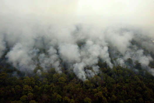 Smoke is seen Tuesday Sept. 6, 2011 in this aerial image over the wildfires in the Bastrop, Texas as the fire continues to spread. Photo: WILLIAM LUTHER, William Luther/wluther@express-news.net / 2011 SAN ANTONIO EXPRESS-NEWS