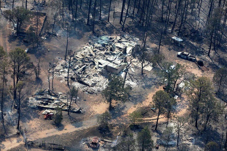 A burned out home is seen at an intersection in this Tuesday Sept. 6, 2011 aerial image taken over the wildfires in the Bastrop, Texas area. Photo: WILLIAM LUTHER, William Luther/wluther@express-news.net / 2011 SAN ANTONIO EXPRESS-NEWS