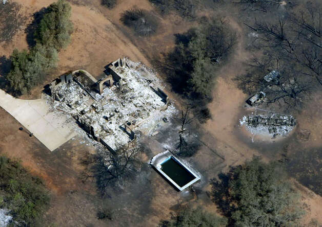 The remains of a fire-destroyed home is seen Tuesday Sept. 6, 2011 in this aerial image over the wildfires in the Bastrop, Texas. Photo: WILLIAM LUTHER, William Luther/wluther@express-news.net / 2011 SAN ANTONIO EXPRESS-NEWS