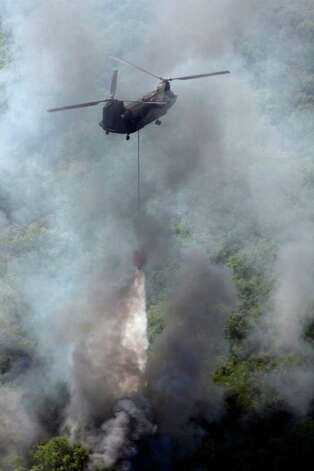 A CH-47 Chinook helicopter drops water Tuesday Sept. 6, 2011 in this aerial image on the wildfires in the Bastrop, Texas. At least two Chinook and three Blackhawk helicopters were assisting in firefighting efforts in the Bastrop area Tuesday. Photo: WILLIAM LUTHER, William Luther/wluther@express-news.net / 2011 SAN ANTONIO EXPRESS-NEWS