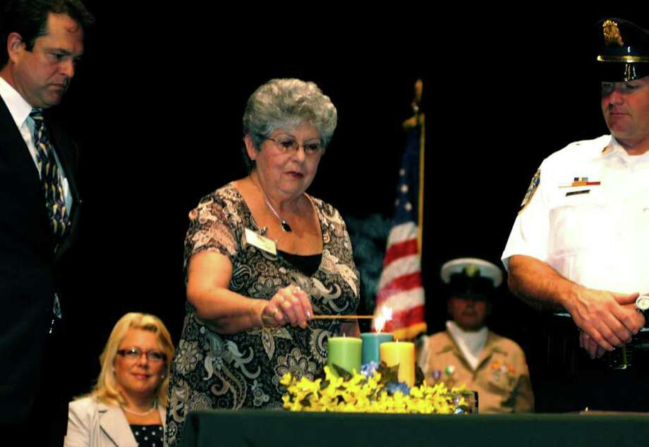Taking care of our own  SPECTRUM/Sharing the honors of lighting three candles symbolizing New Milford's Triad commitment are Michael Gold, left, of GeronNursing & Respite Care from the community's business sector, New Milford Senior Center member Catherine DeLuca and police Chief Shawn Boyne.  Looking on during Monday's Triad ceremony at New Milford High School are Mayor Pat Murphy and VFW color guard member Frank Peet. The ceremony signalled the start of the town's increased dedication to the protection of its elderly. For the story and more photos, see the Aug. 26 edition of The Spectrum. Aug. 15, 2011 Photo: Norm Cummings