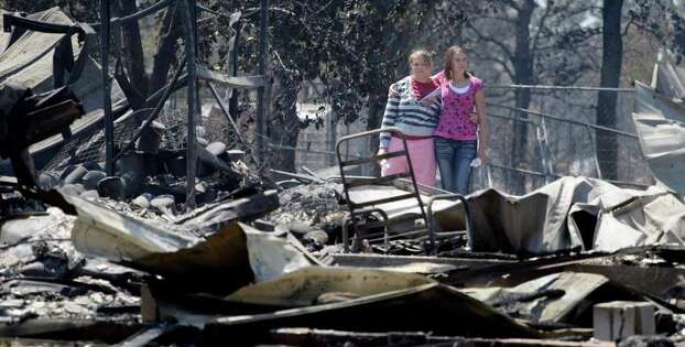 Sisters Laura, left, and Michelle Clements survey their fire-destroyed home, Tuesday, Sept. 6, 2011, in Bastrop, Texas. The Clements lost their home to fires Monday. (AP Photo/Eric Gay) Photo: Eric Gay, STF / AP