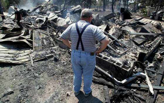 Willie Clements surveys his fire-destroyed home, Tuesday, Sept. 6, 2011, in Bastrop, Texas. Clements lost his home to fires Monday. More than 1,000 homes have burned in at least 57 wildfires across rain-starved Texas, officials said Tuesday. (AP Photo/Eric Gay) Photo: Eric Gay, STF / AP