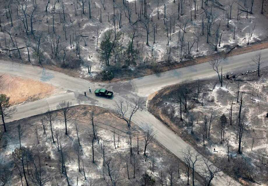 Fire damage is seen in an aerial image taken over the wildfires in the Bastrop, Texas area Tuesday, Sept. 6, 2011.   More than 1,000 homes have been destroyed in at least 57 wildfires across rain-starved Texas, most of them in one devastating blaze near Austin that is still raging out of control, officials said Tuesday.  (AP Photo/San Antonio Express-News, William Luther) Photo: William Luther, MBO / 2011 SAN ANTONIO EXPRESS-NEWS
