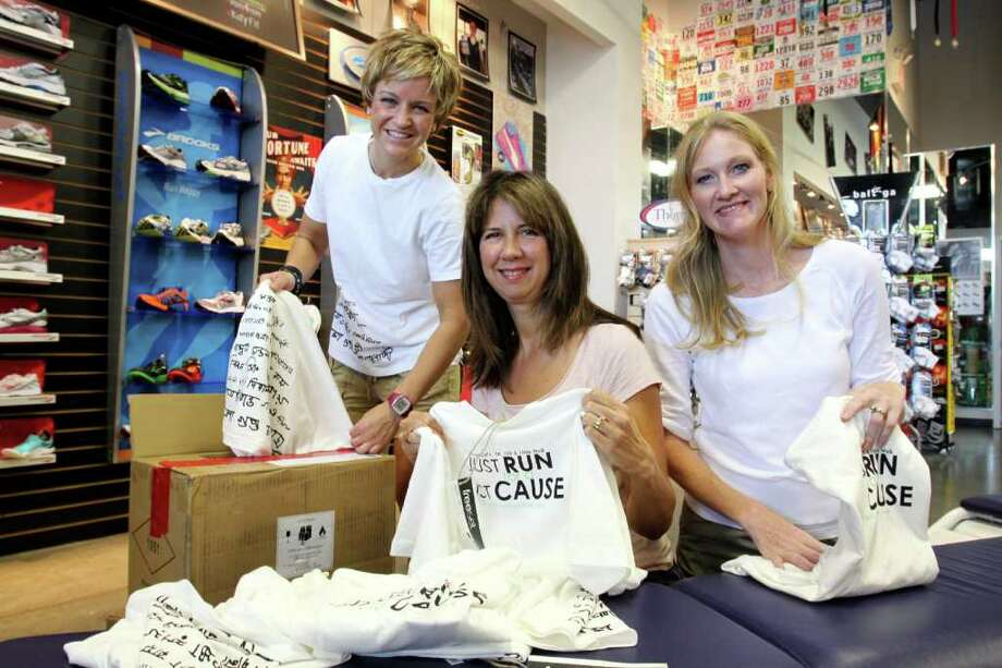 FAMILY FUNDRAISER: Kingsland Baptist Church's Justice Ministry will host a 10K, 5K and one-mile family run beginning at 8 a.m. Sept. 17 at the church, 20555 Kingsland Blvd., to raise money for its human trafficking project. Organizing T-shirts for the event are, from left, Sarah Sallee, Janet Caldwell and Kelly Isenberger. Photo: Suzanne Rehak, Freelance Photographer