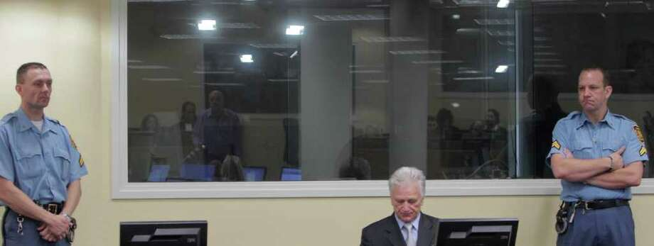 Momcilo Perisic, the former chief of staff of the Yugoslav army, center, waits in the court room of the Yugoslav War Crimes Tribunal in The Hague, to hear the verdict of the court Tuesday Sept 6, 2011. Prosecutors accused Perisic of providing crucial aid to Bosnian Serb forces that allowed them to carry out atrocities including the 1995 massacre of 8,000 Muslim men at Srebrenica and the four-year siege and campaign of shelling and sniping targeting Sarajevo. (AP Photo/Peter Dejong, Pool) Photo: Peter Dejong, POOL / AP