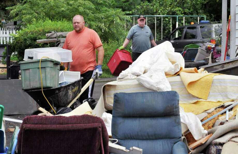 Father and son, Stephen Schlamowitz, Jr., left, and Stephen Schlamowitz, Sr. drag flood ruined possessions to the curb in front of their Route 5S home in Rotterdam Junction Tuesday Sept. 6, 2011, as cleanup efforts continue in the Village after Tropical Storm Irene last week.  (John Carl D'Annibale / Times Union) Photo: John Carl D'Annibale / 00014522A