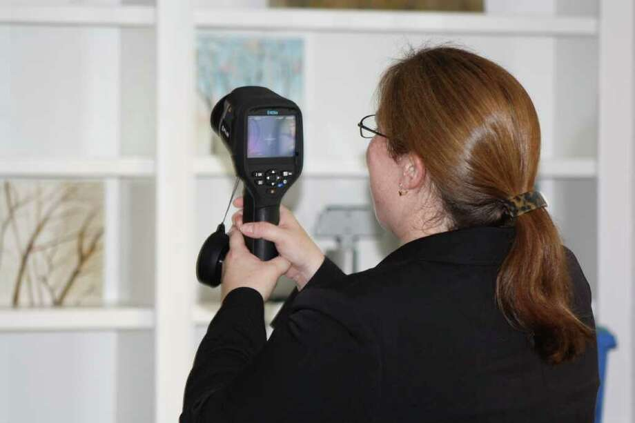 Purva Patel : Chronicle XXXXX: Sheila Courtney, senior risk manager for PURE Insurance, uses an infrared camera to search a new policyholder s home for cold spots that could indicate leaking. Homeowners who install a leak detection system can get a discount on their insurance rate. Photo: Purva Patel