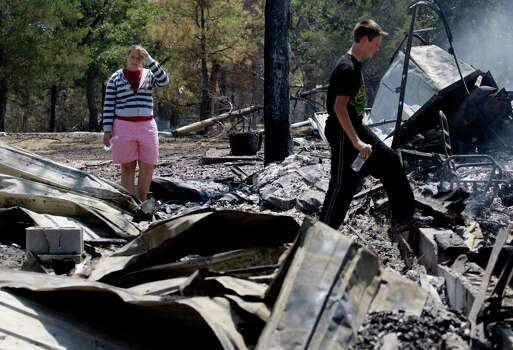 Laura Clements, left, and brother Ben, survey their fire-destroyed home, Tuesday, Sept. 6, 2011, in Bastrop, Texas. (AP Photo/Eric Gay) Photo: Eric Gay, Associated Press / AP