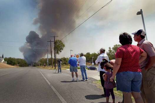 Residents view the wild fire  along Highway 21 near Highway 95  on Tuesday, Sept. 6, 2011 in Bastrop, Texas.  More than 1,000 homes have been destroyed in at least 57 wildfires across rain-starved Texas, most of them in one devastating blaze near Austin that is still raging out of control, officials said Tuesday.  (AP Photo/Austin American-Statesman, Ralph Barrera)  MAGS OUT; NO SALES; TV OUT; INTERNET OUT; AP MEMBERS ONLY Photo: Ralph Barrera, Associated Press / Austin American-Statesman