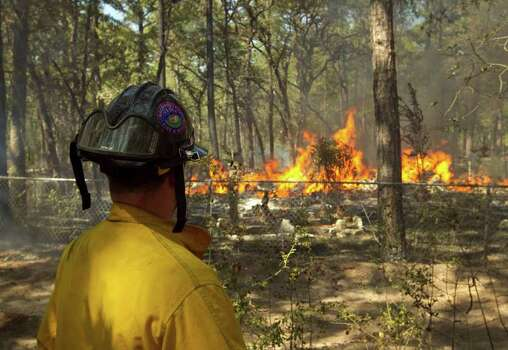 Firefighter Todd Jamison of the Little Elm Fire Department watches a home burn to the ground on Pine Tree Loop in Bastrop, Texas  on Tuesday Sept. 6, 2011. (AP Photo/Austin American-Statesman, Jay Janner) Photo: Jay Janner, Associated Press / Austin American-Statesman
