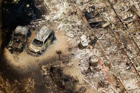 A burned out house and cars are seen in the Remington Forest subdivision near Magnolia, Texas, on Tuesday, Sept. 6, 2011. A large blaze burning in forests in Montgomery, Waller and Grimes counties north and west of Houston contributed to  more than 1,000 homes that have been destroyed in at least 57 Texas fires.