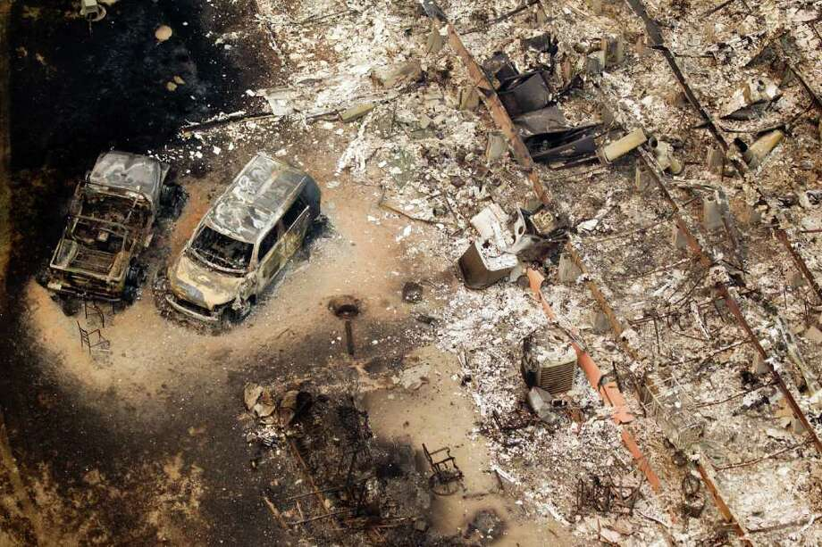 A burned out house and cars are seen in the Remington Forest subdivision near Magnolia, Texas, on Tuesday, Sept. 6, 2011. A large blaze burning in forests in Montgomery, Waller and Grimes counties north and west of Houston contributed to  more than 1,000 homes that have been destroyed in at least 57 Texas fires. Photo: Smiley N. Pool, Houston Chronicle / © 2011  Houston Chronicle