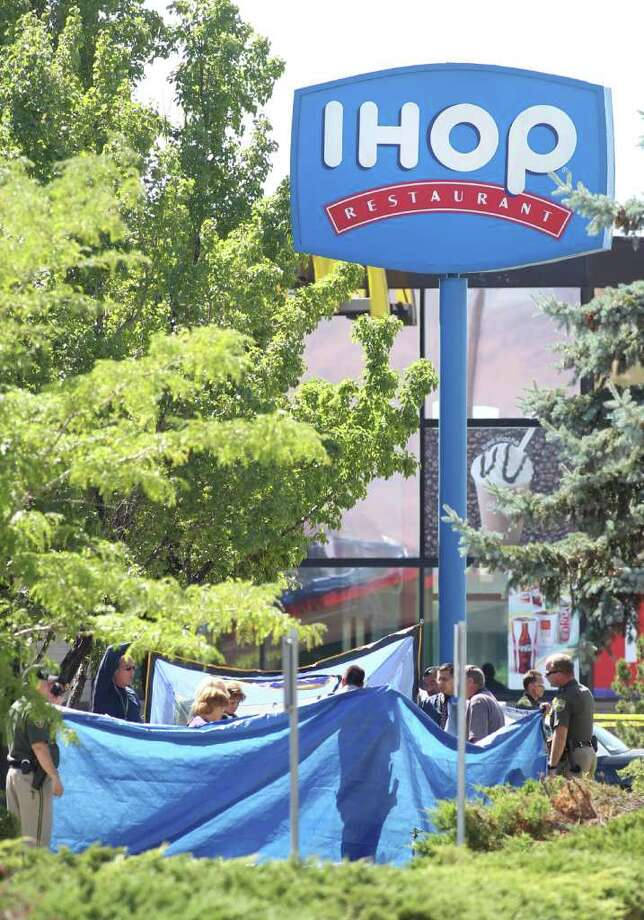 Officials investigate the scene of a shooting in an IHOP restaurant in Carson City, Nev., on Tuesday, Sept. 6, 2011.   A gunman with a rifle opened fire at a International House of Pancakes restaurantkilling three people including two uniformed National Guard members and himself, and wounding six others in a hail of gunfire during the morning breakfast hour, authorities and witnesses said.  (AP Photo/Cathleen Allison) Photo: Cathleen Allison, FRE / FR70203 AP