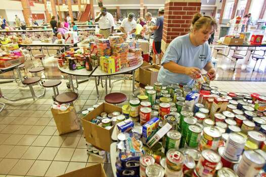 Amy Barton, a Magnolia Independent School District employee, volunteers her time to organize food donated to the Red Cross' evacuation center, Tuesday, Sept. 6, 2011, in Montgomery County. Photo: Nick De La Torre, Houston Chronicle / © 2011 Houston Chronicle