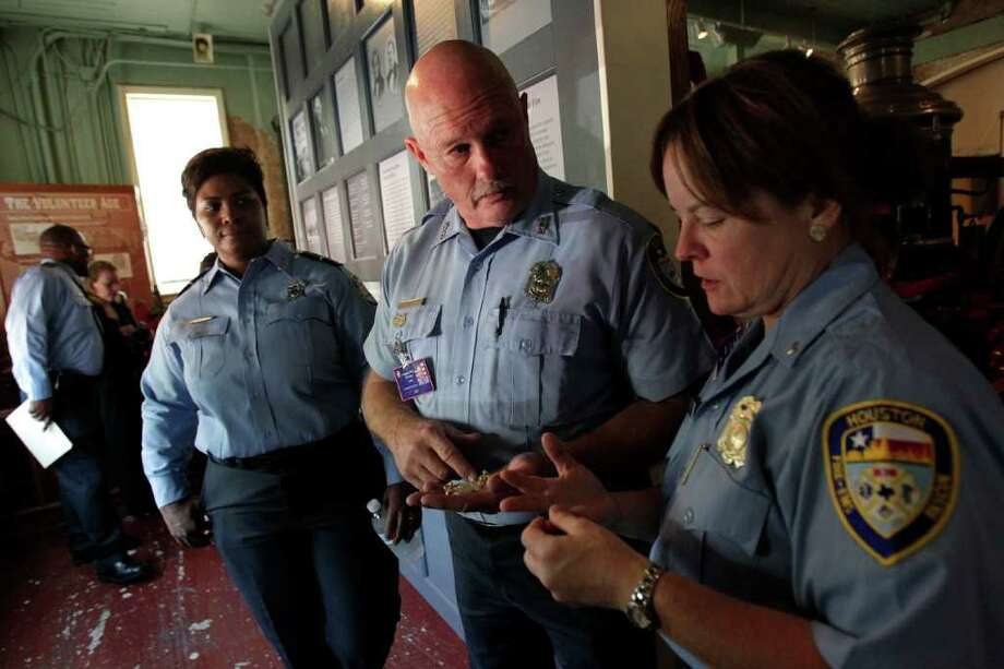 "JOHNNY HANSON PHOTOS : CHRONICLE GOING TO NYC: Houston firefighter Gretchen Wolf, right, and engineer operator James Wathen count the number of honor guard pins they will need for their trip to New York City, where they'll perform  a ""line of honor"" during ceremonies for the 10th anniversary of Sept. 11. Photo: Johnny Hanson, Staff / © 2011 Houston Chronicle"