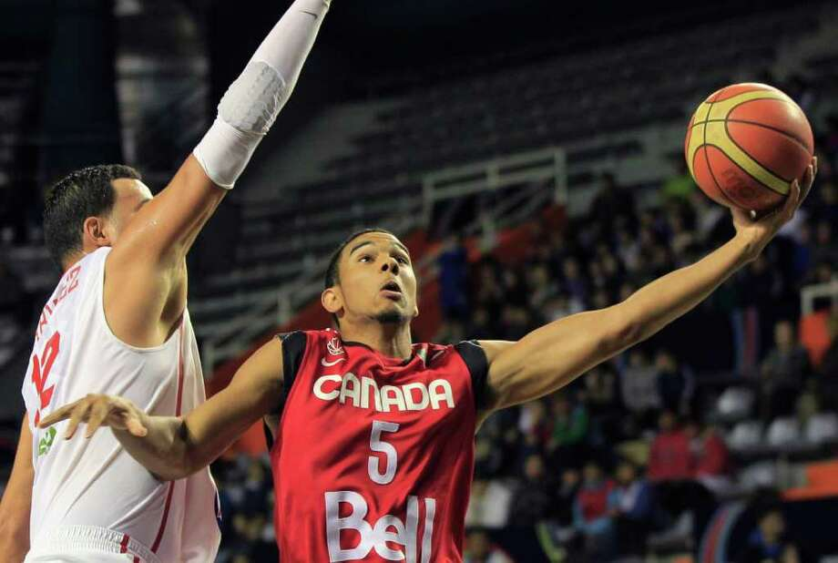 Canada's Cory Joseph, right, goes for a layup against Puerto Rico's Manuel Narvaez during a FIBA Americas Championship basketball game in Mar del Plata, Argentina, Tuesday, Sept. 6, 2011. The top two finishers of the tournament get an automatic berth in the 2012 London Olympics and the next three advance to the last-chance Olympic qualifier to be held in July 2012. Photo: Martin Mejia/Associated Press