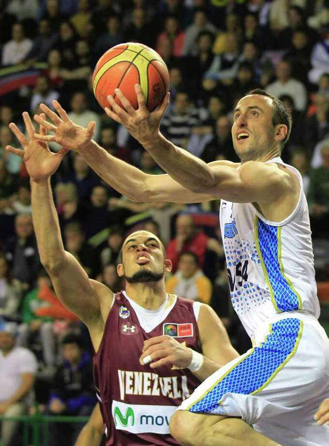 Argentina's Manu Ginobili, right, goes up for a shot over Venezuela's Jose Bravo during a FIBA Americas Championship basketball game in Mar del Plata, Argentina, Tuesday, Sept. 6, 2011. The top two finishers of the tournament get an automatic berth in the 2012 London Olympics and the next three advance to the last-chance Olympic qualifier to be held in July 2012. Photo: Martin Mejia/Associated Press