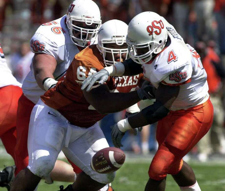 Texas' Casey Hampton causes a fumble from Oklahoma State's Reggie White during the second quarter in 2000. Hampton started 37 straight games and led UT's defense in tackles for two straight seasons. Photo: Courtesy Photo/University Of Texas / University of Texas