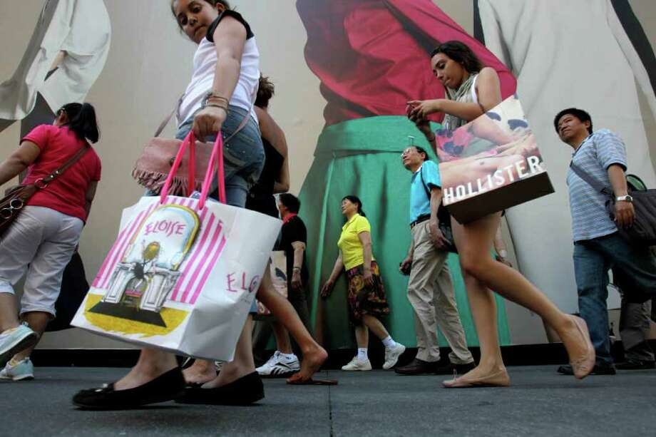 FILE - In this July 5, 2011 file photo, pedestrians carrying shopping bags make their way along Fifth Avenue in New York. As the down economy batters both teens and their parents, teen clothing chains are having mixed success as they try to attract young people back into their stores by offering more of the things they love.  (AP Photo/Seth Wenig, File) Photo: Seth Wenig / AP2011