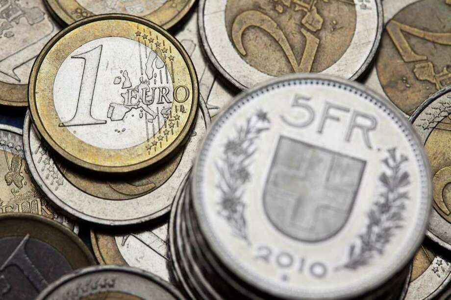 """FILE - The July 14, 2011 file photo shows coins of Swiss francs and euros in Zurich, Switzerland. The Swiss National Bank set a ceiling on the value of the country's strong currency on Tuesday, using what experts called a last-ditch """"nuclear option"""" to protect its economy and keep exporters competitive. The bank said it would spend whatever it takes to keep the currency from strengthening beyond 1.20 francs per euro and indicated it might take more measures to weaken it further. (AP Photo/Keystone, Martin Ruetschi) Photo: Martin Ruetschi / KEYSTONE"""