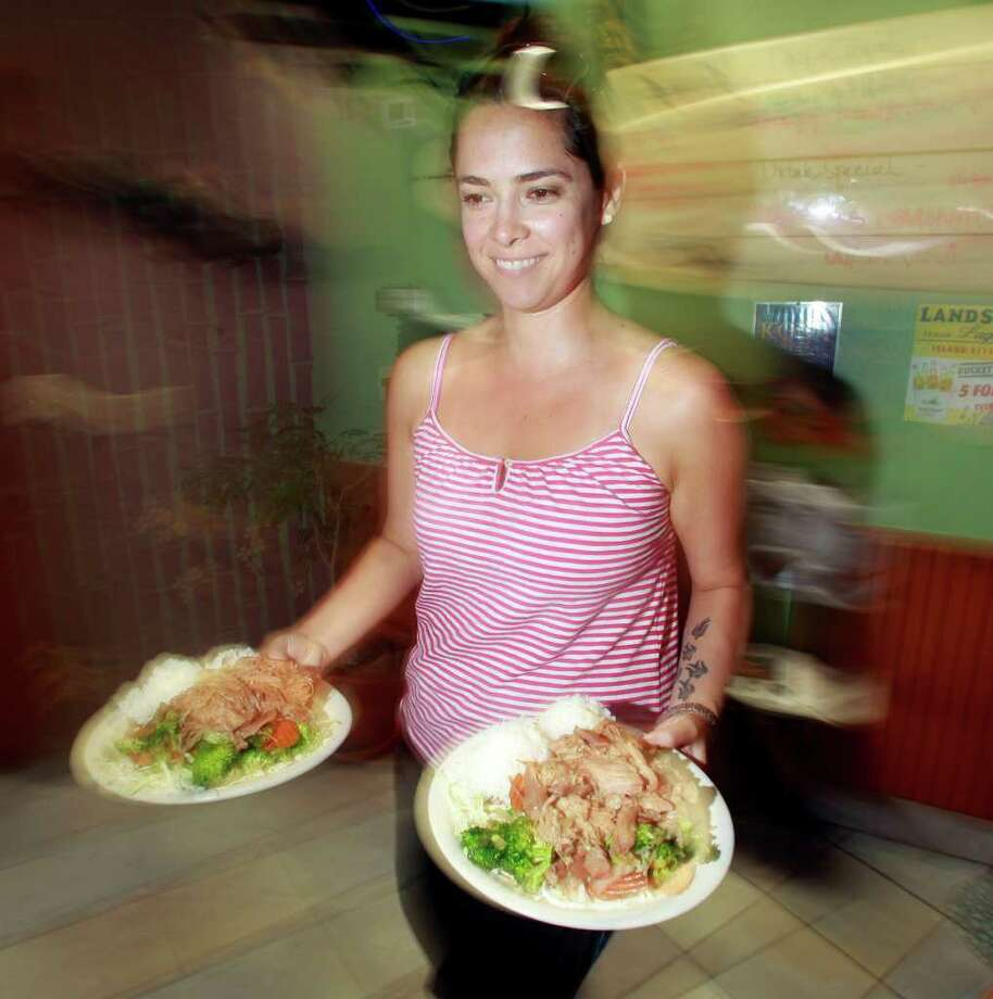 In this  Sept. 3, 2011 photo, waitress Jamie Romero plates food to a table at the Bamboo Grove Hawaiian Grille, in Portland, Ore. Service firms grew at slightly faster pace in August compared to July, but the sector remains weak.(AP Photo/Rick Bowmer) Photo: Rick Bowmer